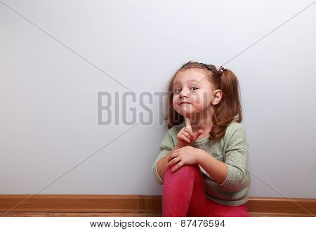 Fun Smiling Sitting Kid Girl Thinking With Finger Near Face