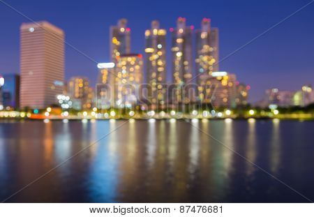 Out of focus big city lights at night time with water reflection