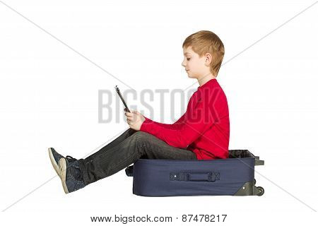 Boy Sitting In Travel Bag Using Tablet Pc Isolated On White