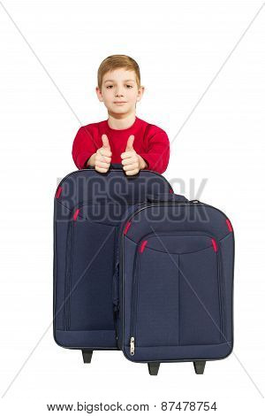 Portrait Of Boy Showing Thumbs Up With Travel Bags