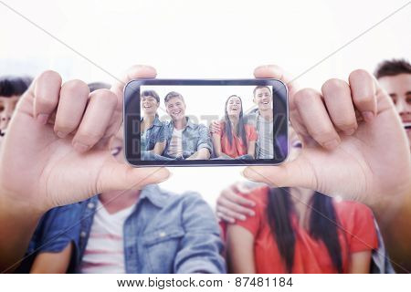 Hand holding smartphone showing against a group of laughing friends look into the camera