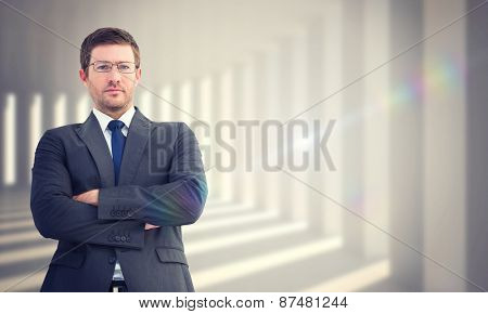 Frowning businessman looking at camera against curved white room