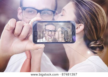 Hand holding smartphone showing against young woman kissing man