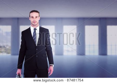 Serious businessman standing and holding briefcase against room overlooking ocean