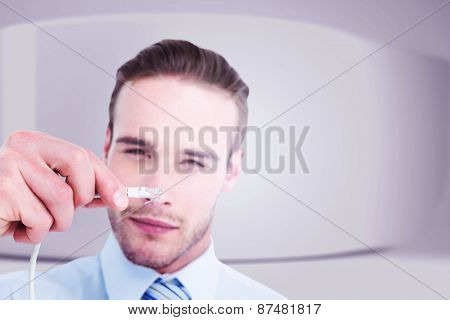 Concentrated businessman holding a cable against white abstract room