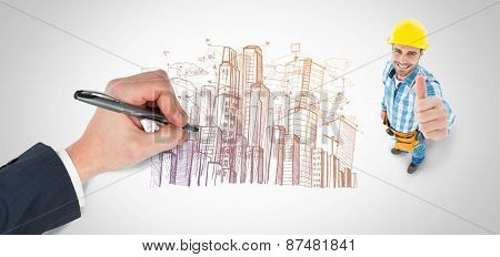 Hand writing with a pen against large city buildings together