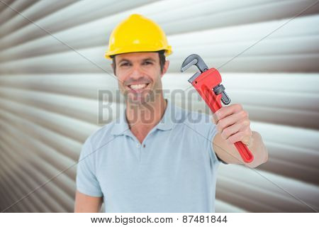 Happy carpenter holding monkey wrench against grey shutters
