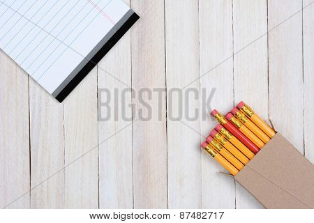 High angle shot of a box of pencils and a writing tablet on a white wood surface. Objects are in opposite corners of the frame.