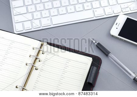 Personal Organizer Address Book With Pen And Smart Phone On Computer Desk