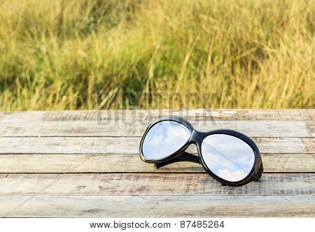 Clear Sky In Eyeglasses On The Wooden Background