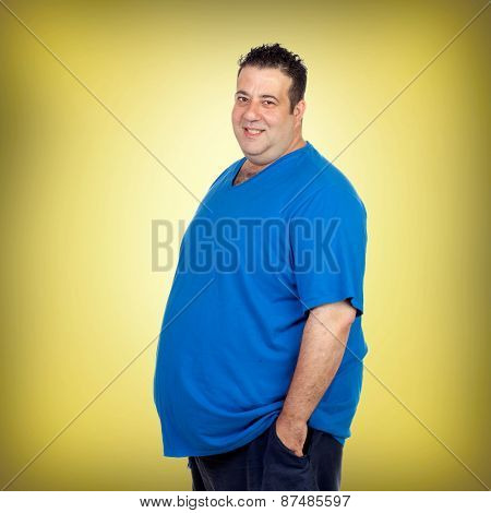Happy fat man with blue shirt and a yellow background