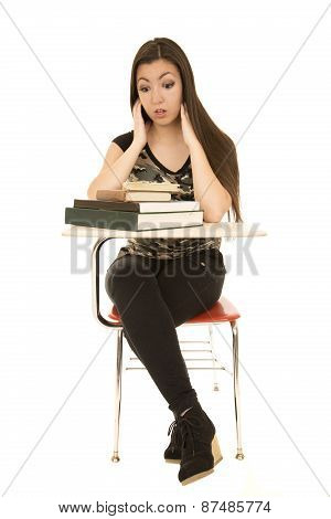 Girl Sitting At School Desk With Overloaded Expression