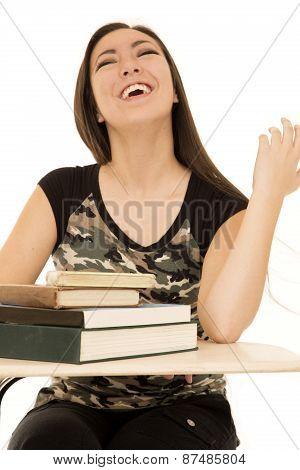 Female Student Sitting At Desk Full Of Books Laughing