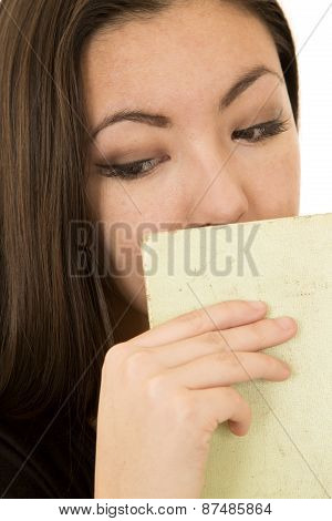 Young Female Looking Down Hiding Mouth With Book