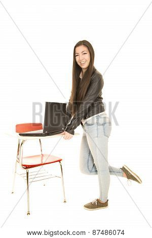 Cute Teenage Girl Standing By A Desk With A Computer