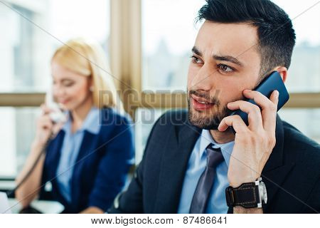 Close Up Of A Young Business Man Who Talks On The Phone With Business Woman In The Background That I