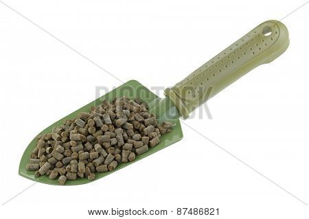 A shovel full of compressed Organic Animal-based Fertilizer Pellets isolated on white