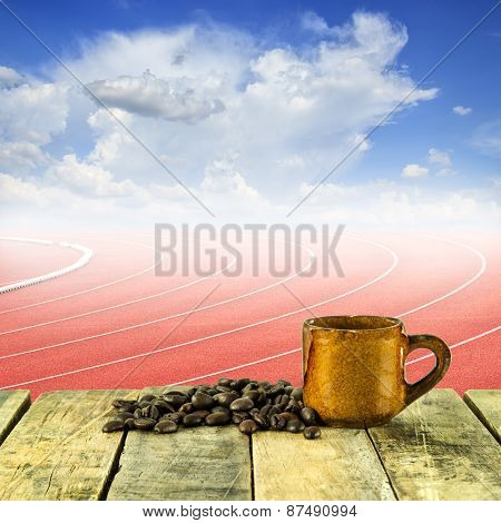 Coffee Cup And Coffee Beans At Curve Of A Running Track