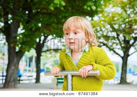 Adorable toddler boy having fun on playground, wearing bright green pullover