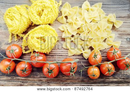 Bunch of small red cherry tomatoes with raw pasta Reginette (Mafaldine) and butterfly shaped pasta f
