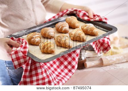 Croissant on pan in hands
