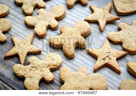 Gingerbread cookies in shapes of heart, star and man on wooden table