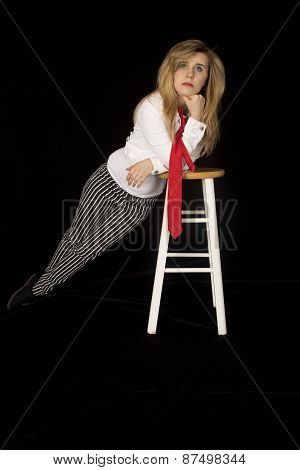 Female Model Leaning On A Barstool Looking At Camera Black Background