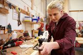 picture of carpentry  - Female Apprentice Planing Wood In Carpentry Workshop - JPG