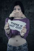 stock photo of kidnapped  - Female teenager a kidnap victim holding a paper with a text THERE IS NO GOD - JPG