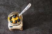 pic of muse  - A jar of healthy swiss museli yogurg blackberries and honey on a black slate background - JPG