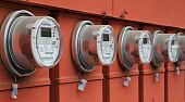 picture of electricity meter  - Line up of five electric power meters on red electrical panels - JPG