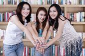 image of joining hands  - Portrait of beautiful female students standing in the library while joining their hands - JPG