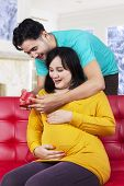 foto of wifes  - Portrait of asian man giving a gift to his expectant wife on the sofa at home - JPG