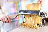 foto of noodles  - Woman making noodles with pasta machine - JPG