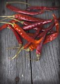 stock photo of red hot chilli peppers  - Red hot chili peppers on an old wooden table texture. Spicy pepper. Food photography with cope space. Shallow depth of field, selective focus ** Note: Shallow depth of field - JPG