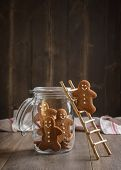 stock photo of gingerbread man  - Gingerbread man on rustic ladder climbing into cookie jar - JPG