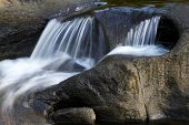 stock photo of flow  - Water flowing over rocks in stream - JPG