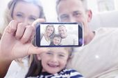 picture of cuddle  - Hand holding smartphone showing against parent cuddling their son on the couch - JPG