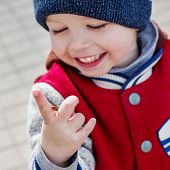 picture of ladybug  - Toddler smiling child looking at a ladybug on her hand - JPG