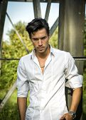 picture of single man  - Handsome young man leaning against metal electricity trellis wearing white shirt - JPG