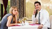 picture of boring  - Woman is bored at restaurant, her boyfriend talks on the phone
