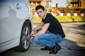 stock photo of squatting  - Handsome Young Man in Casual Clothing Squatting Besides the Wheel of a his White Car Changing Tires While Looking at the Camera Seriously - JPG