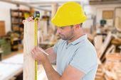stock photo of carpenter  - Carpenter using measure tape to mark on wooden plank against workshop - JPG