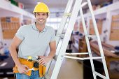 stock photo of step-ladder  - Worker holding tools while leaning on step ladder against workshop - JPG