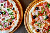foto of hot fresh pizza  - Two big hot and tasty pizzas with olives and salami - JPG