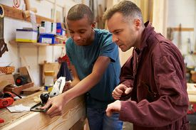 picture of joinery  - Carpenter With Apprentice Planing Wood In Workshop - JPG
