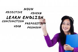 foto of verbs  - Portrait of beautiful teenage student studying foreign language and write english material - JPG
