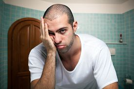 stock photo of deprivation  - Portrait of a tired man looking in the mirror in the bathroom - JPG