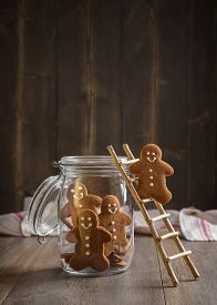 stock photo of gingerbread man  - Gingerbread man on rustic ladder climbing into cookie jar - JPG
