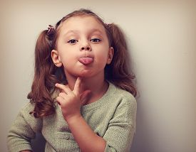 stock photo of tongue  - Thinking grimacing girl showing tongue with finger under face and looking funny in camera - JPG